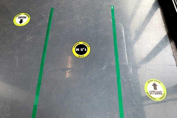 In en uitgang corona vloersticker looproutes