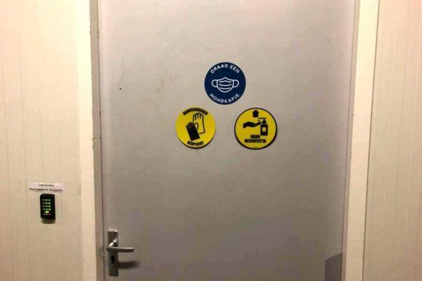 sticker handen desinfecteren verplicht corona maatregelen toepassing deur